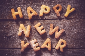 Happy New Year text with cookies on the wooden background from above